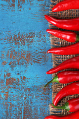 Red hot chili peppers on color wooden background