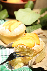 Tasty mini cakes with fresh peach, on table