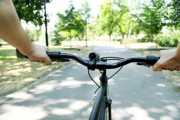 Man biking fast in city park.  View from bikers eyes
