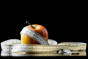 Apple wrapped in a tape measure  over black
