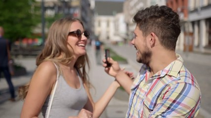 Cheerful young couple on a city street - meeting/date