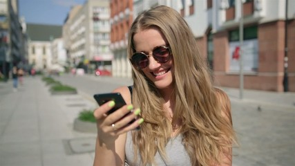 Young happy woman texting on mobile phone during sunny day