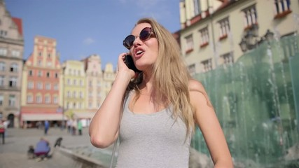 Cheerful woman talking on mobile phone in the city.
