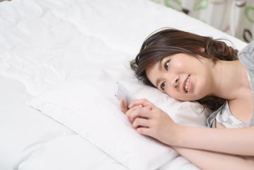 ベッドに寝そべってスマートフォンを見る女性