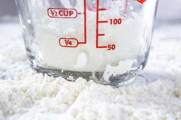 White flour and measuring cup on table.
