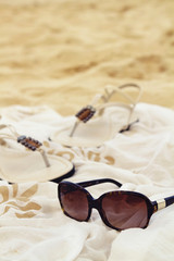 Sunglasses sarong sandals on the beach