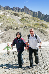 The elderly couple with boy walk in Alps