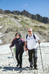 The mature couple walk in mountains