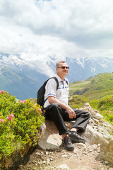 Mature man sits on top of a mountain