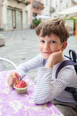 Nine years boy eating berry ice cream at outdoor cafe