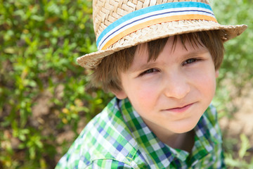 Portrait of the small boy with hat in a sunny day
