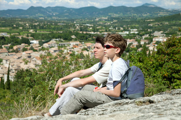 The young boy and adult man sit on top of hill