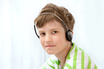 Young boy listening music on headphones and smiling