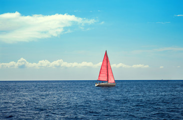 The boat with pink sail in calm blue sea