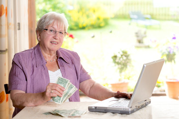 older woman with money and computerfriendly