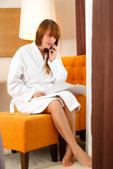 Young woman talking on the phone and sitting on sofa in hotel ro