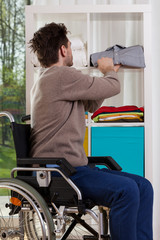 Disabled man placing shirt on shelf
