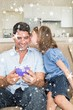 Composite image of girl kissing father holding gift box on sofa