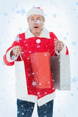 Composite image of festive man holding shopping bags