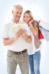 Composite image of happy couple holding shopping bags and cash