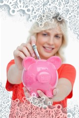 Blonde woman putting notes into a pink piggy bank