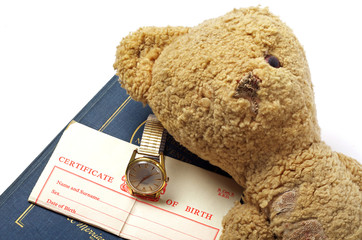 birth certificate and worn out teddy bear