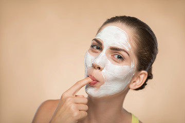 Beautiful girl applying facial cream mask and beauty treatments