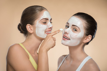 Two beautiful girls applying facial cream mask and beauty treatm