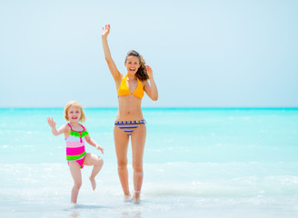 Mother and baby girl waving with hand on sea coast