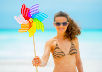 Closeup on smiling young woman holding colorful windmill toy
