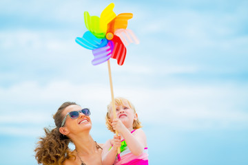 Happy mother and baby girl holding colorful windmill toy