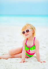 Baby girl in sunglasses sitting on beach