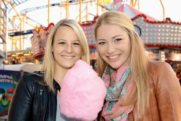 Freundinnen essen Zuckerwatte auf Jahrmarkt
