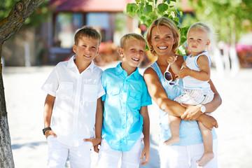 Happy mother with children standing outdoor.