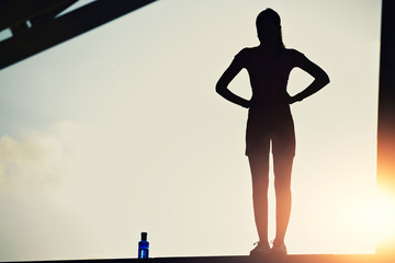 Silhouette of female runner on beautiful sunset sky background