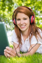 Redhead using her tablet pc while listening to music