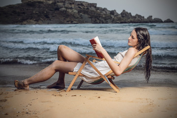 girl reading a good book at the beach