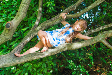 Cute little girl playing outdoors, claiming on a tree