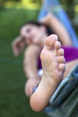 feet of a girl relaxing in a hammock in the backyard
