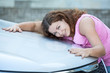 Smiling attractive woman embracing car hood with hands