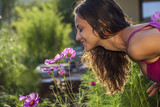 Fototapety Young beautiful woman smells a flower in the garden