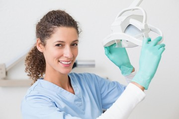 Dentist in blue scrubs smiling at camera beside light