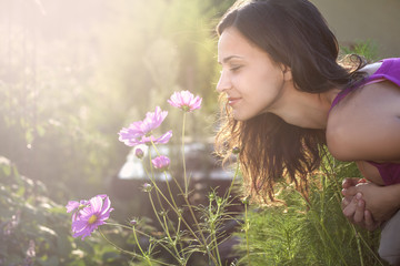 Young beautiful woman smells a flower in the garden