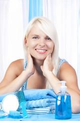 Junge Frau im Bad mit Pflegeartikeln