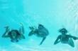 Friends underwater in swimming pool