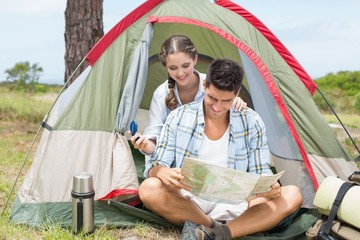 Couple looking at map outside their tent
