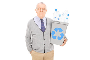 Senior man holding a recycle bin full of plastic bottles