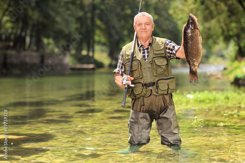 Proud fisherman holding fish in a river - 69759328