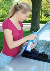 Frau bei Autowäsche mit Scheibenreiniger