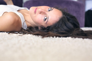 beautiful young woman lying on the carpet